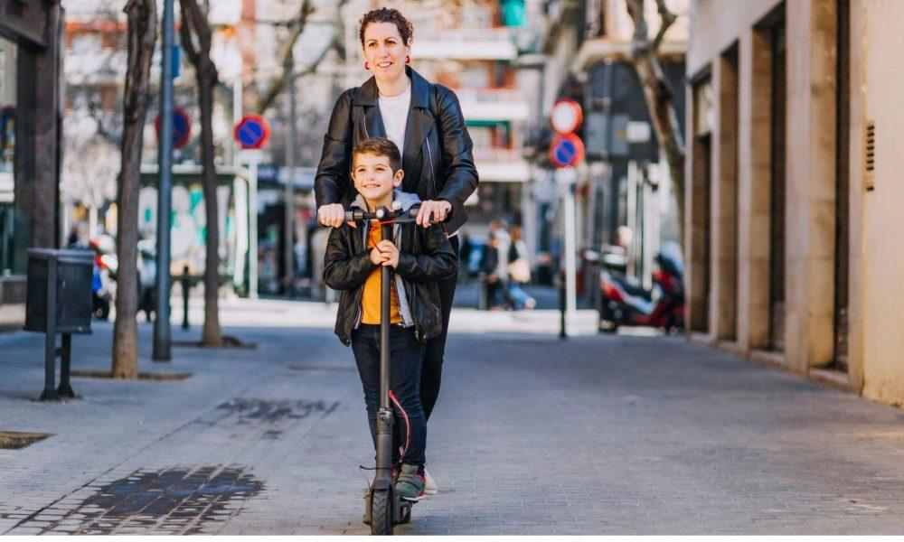 Une mère et son fils sur une trottinette électrique.